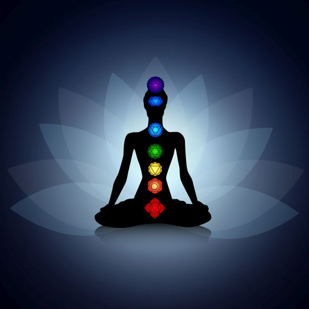 A person sitting and meditating with chakras