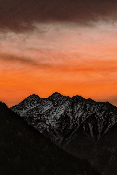 A mountain with a red sunset